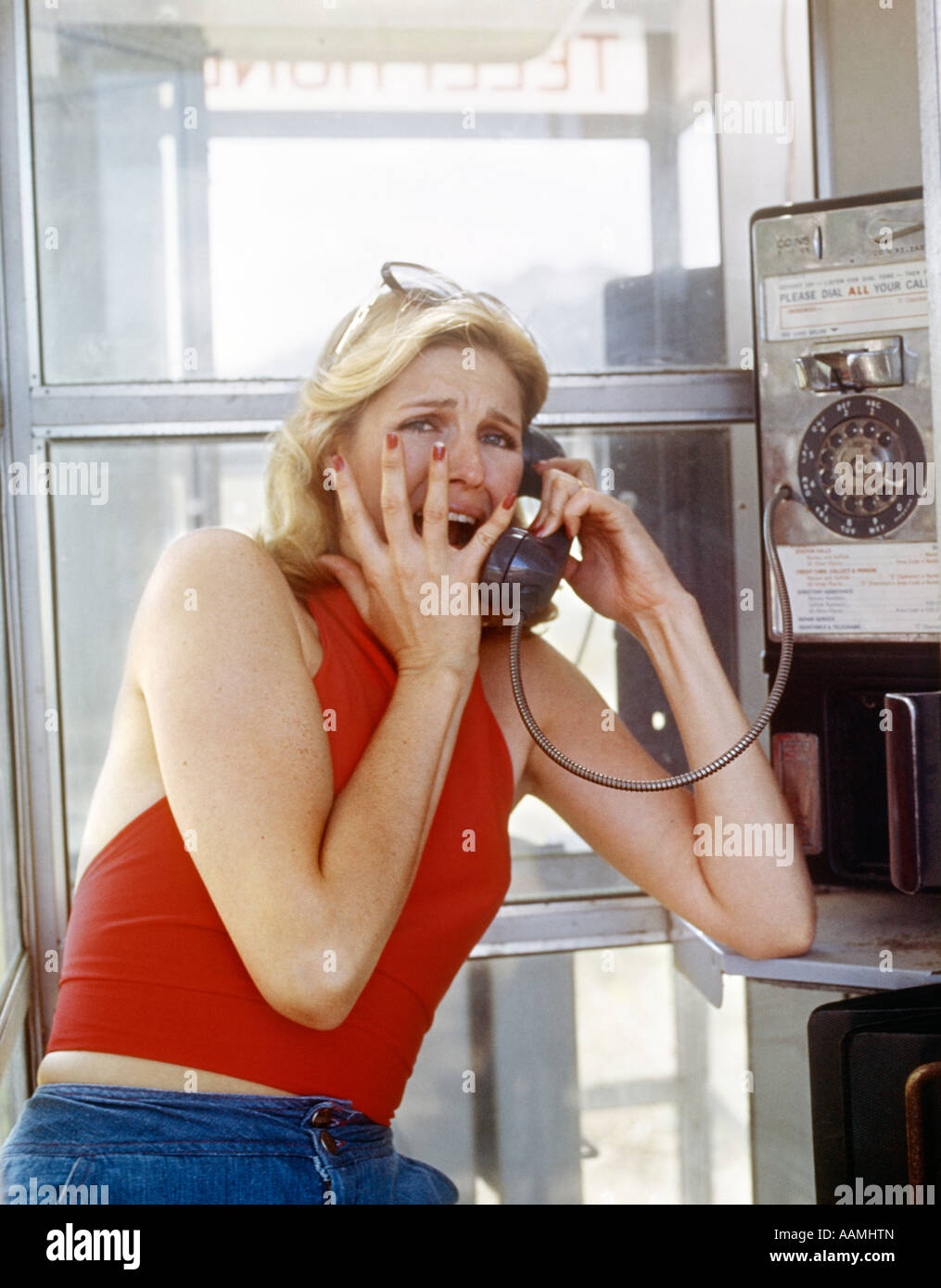 RETRO BLONDE WOMAN SCREAMING TERRIFIED IN PAY TELEPHONE BOOTH CRIME MYSTERY DANGER VICTIM ASSAULT INJURY PAIN RED - Stock Image