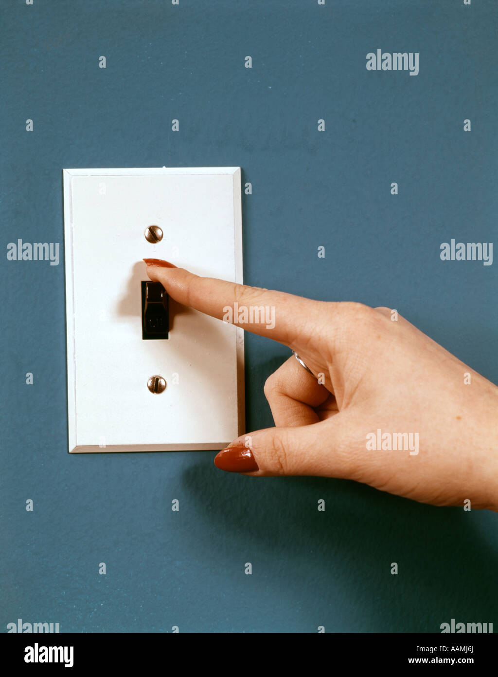 LIGHT SWITCH HAND ON OFF ELECTRICITY 1970 1970s RETRO - Stock Image