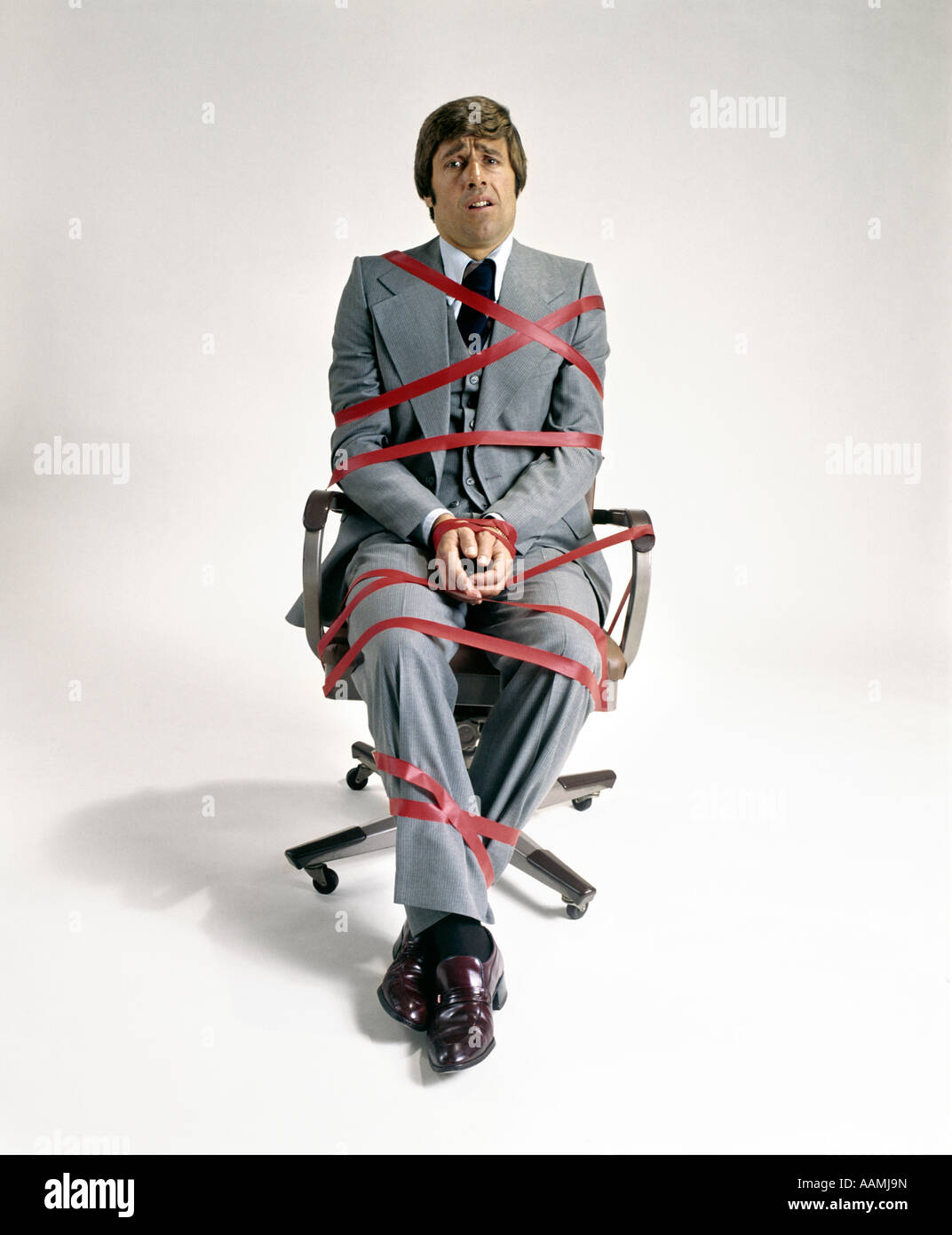 1970s BUSINESS MAN TIED UP IN RED TAPE SITTING IN OFFICE DESK CHAIR SYMBOLIC - Stock Image