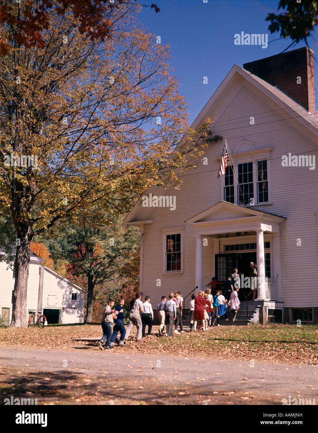 SCHOOL CHILDREN WALKING INTO SCHOOLHOUSE 1970s - Stock Image