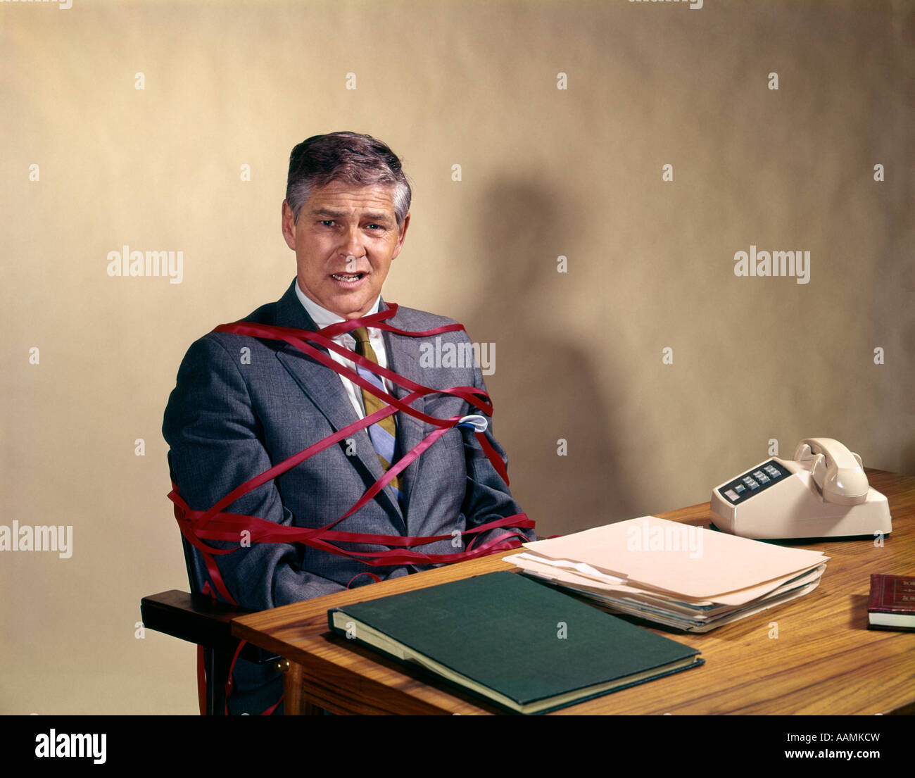 1970s MIDDLE AGED BUSINESS MAN AT DESK TIED UP TANGLED IN RED TAPE OFFICE SNAFU BUREAUCRACY WASTEFUL RETRO VINTAGE - Stock Image