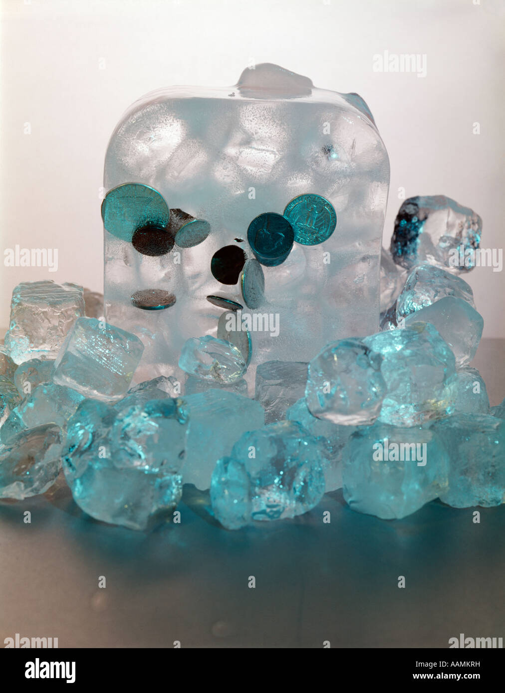 BLOCK OF ICE WITH COINS FROZEN INSIDE IMBEDDED COLD CASH FROZEN ASSETS FINANCE ICE CUBES FREEZE ACCOUNTS RETRO VINTAGE - Stock Image