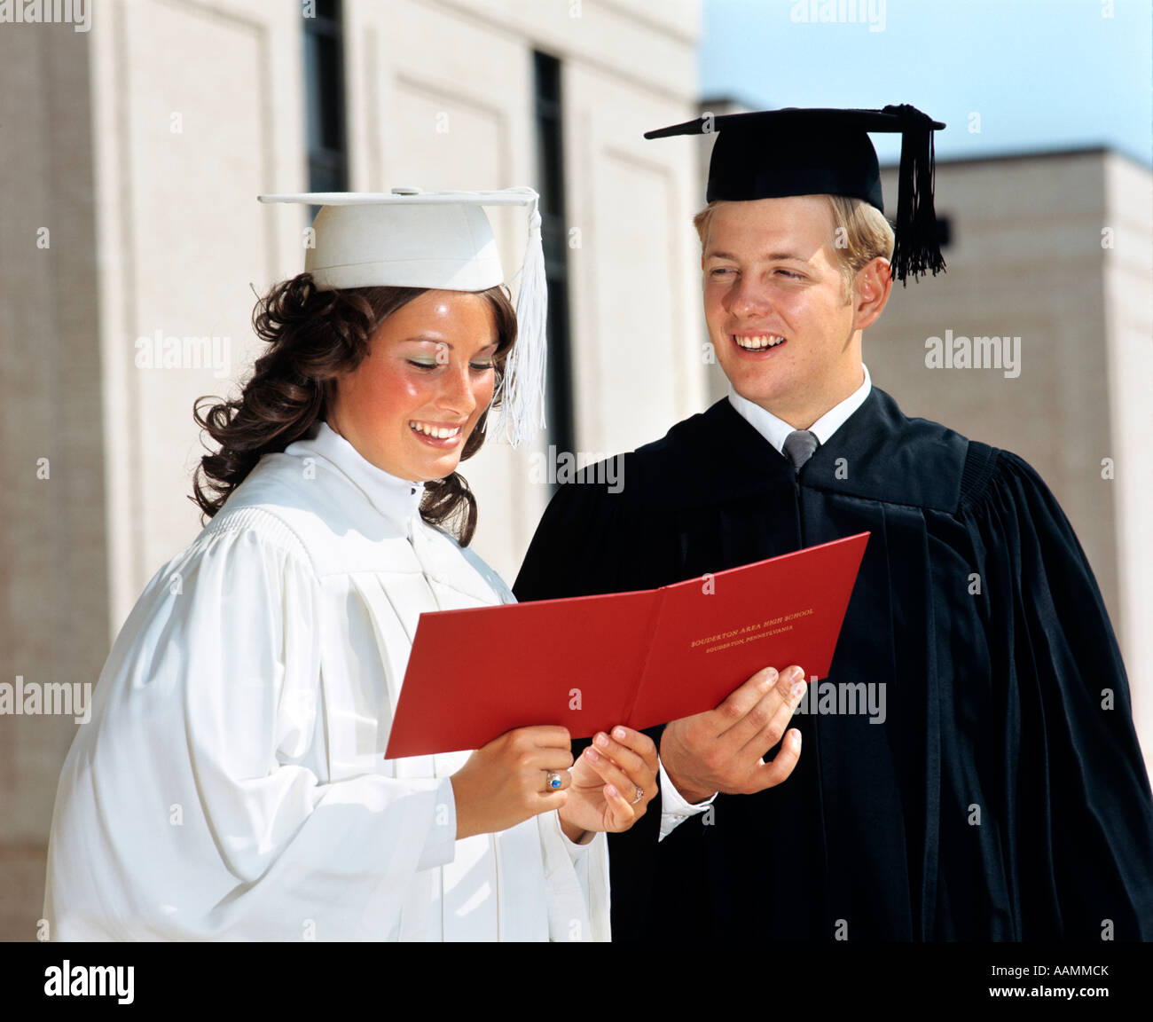 4252fb03dbf 1970s TEEN COUPLE GIRL WHITE ROBE BOY IN BLACK ROBE MORTARBOARD HOLD RED  DIPLOMA BETWEEN THEM