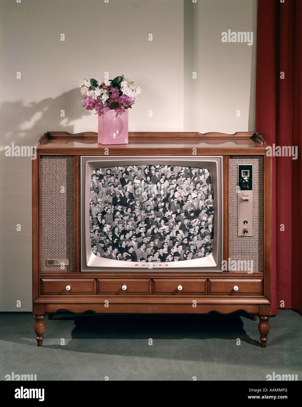 1960s LARGE CONSOLE TELEVISION WITH BLACK AND WHITE SCREEN IMAGE AND VASE OF FLOWERS ON TOP NOSTALGIA - Stock Image