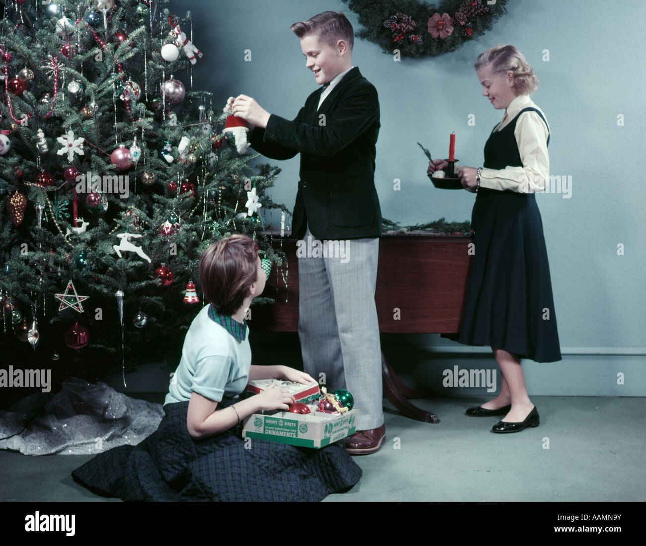 1950s TWO GIRLS AND ONE BOY DECORATING CHRISTMAS TREE WITH ORNAMENTS ...