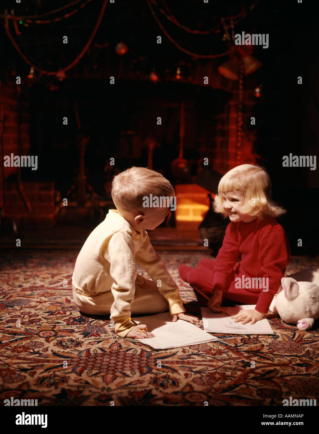 1940s 1950s LITTLE BOY AND GIRL IN PAJAMAS SMILING TOGETHER ON RUG IN FRONT OF A CHRISTMAS FIRE IN FIREPLACE RETRO - Stock Image