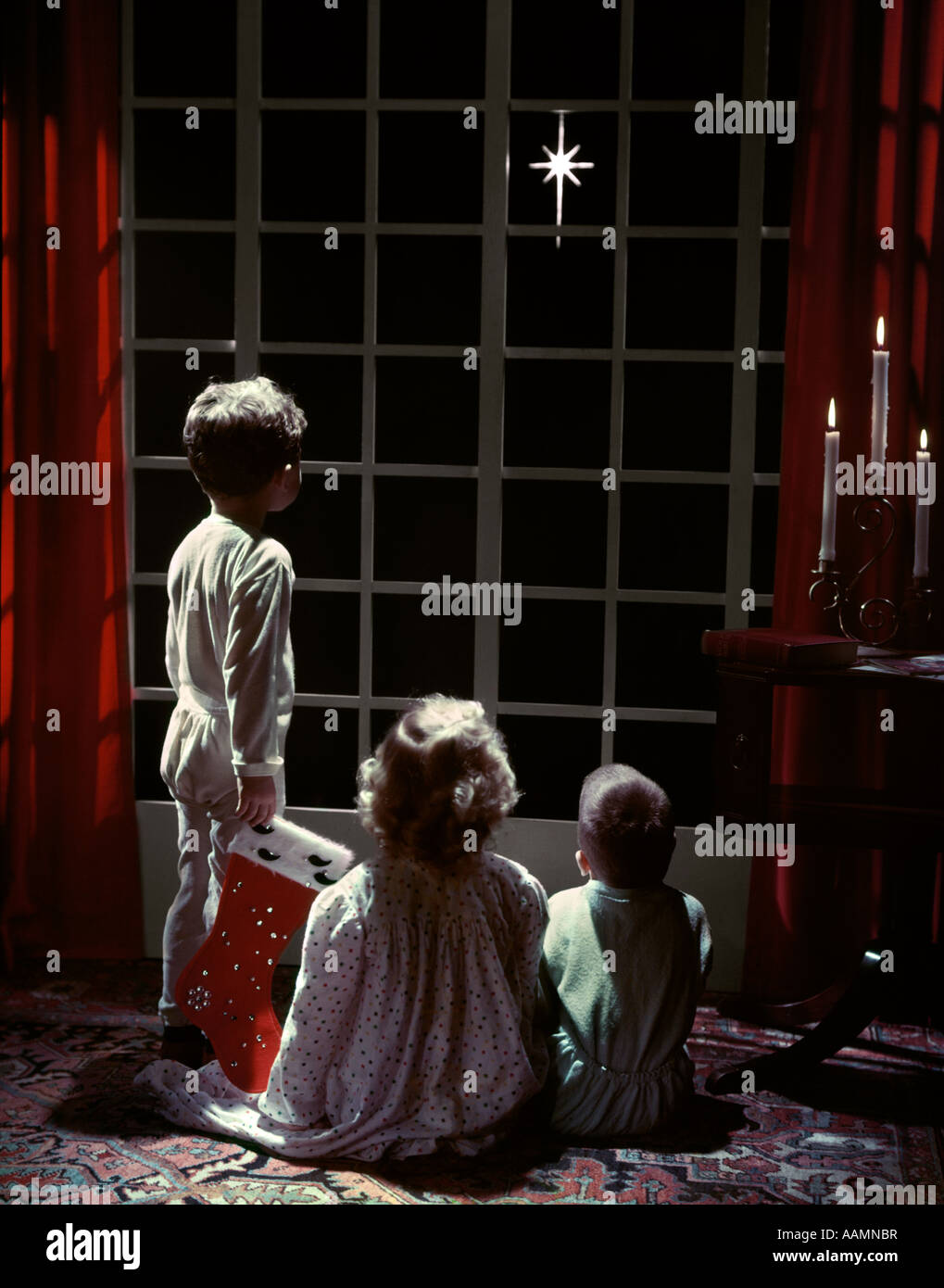 1950s 3 children 2 boys 1 girl pajamas look out french doors to star bethlehem christmas eve boy holds stocking studio - Children Christmas Pictures 2