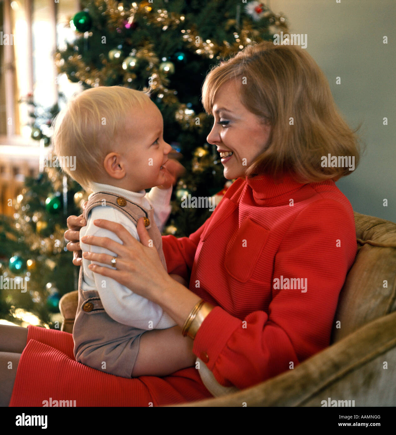 1970 1970s WOMAN MOTHER SMILING BABY LAP PARENT PARENTING CHRISTMAS TREE HOLIDAY BABY FIRST FAMILY FAMILIES RETRO - Stock Image