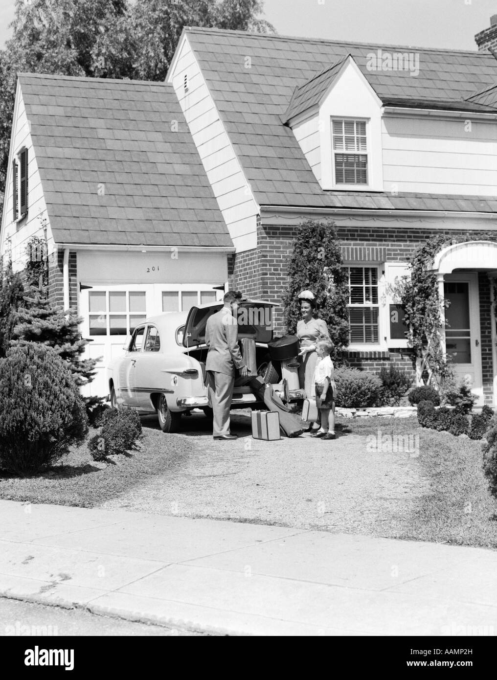 1950s FAMILY MOTHER FATHER SON IN FRONT OF SUBURBAN HOUSE LOADING CAR TRUNK WITH LUGGAGE SUITCASE GOLF BAG TRIP - Stock Image
