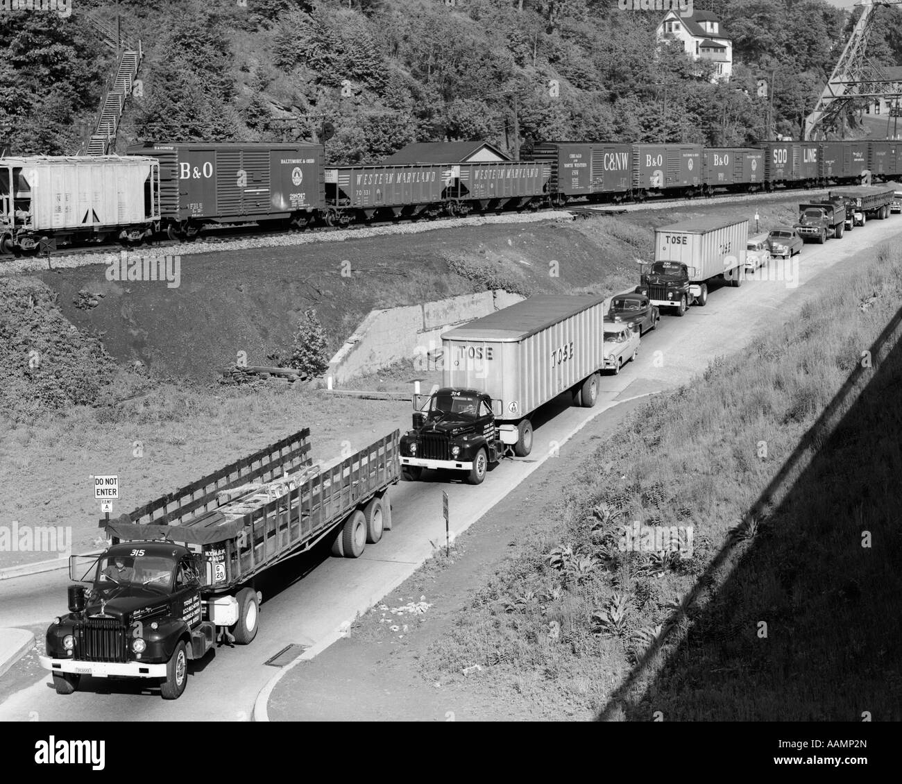 1950s LINE OF TRAFFIC WITH MANY TRUCKS & CARS & FREIGHT TRAIN PASSING ON ADJACENT HILLSIDE - Stock Image