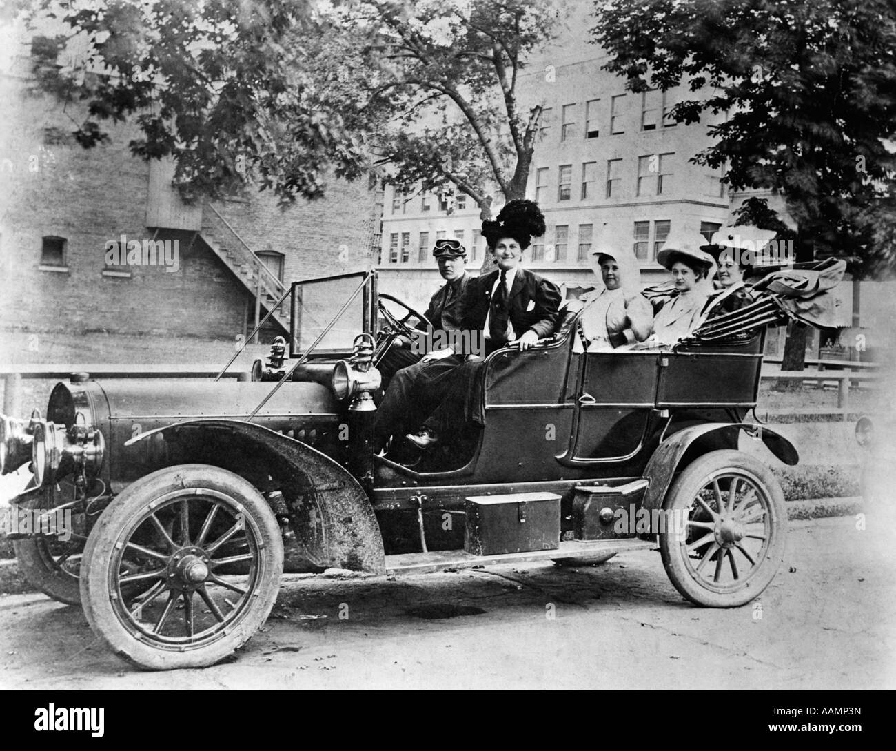 1910s GROUP OF FIVE SITTING IN CAR PARKED ON STREET MAN IN FRONT SEAT WEARING CAP WITH GOGGLES FOUR WOMEN WEARING - Stock Image