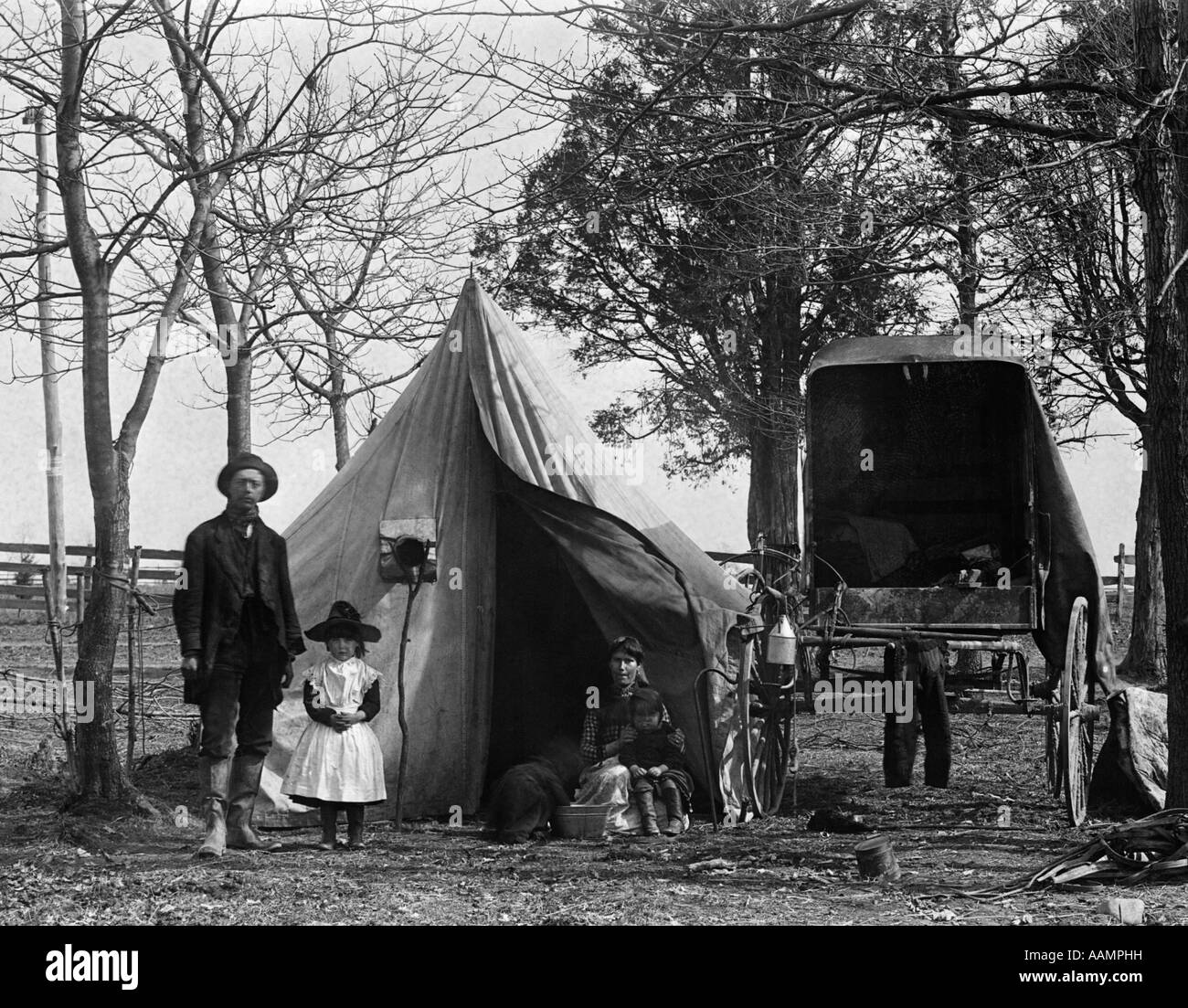 19TH CENTURY GYPSY CAMP FAMILY FATHER MOTHER DAUGHTER IN FRONT OF TENT NEXT TO WAGON - Stock Image