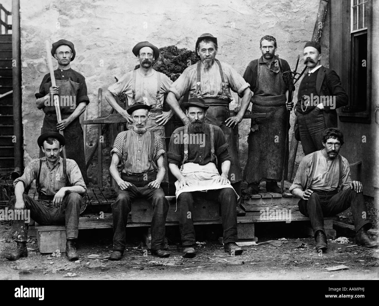1890s 1900s GROUP PORTRAIT OF 9 CARPET MILL WORKERS - Stock Image