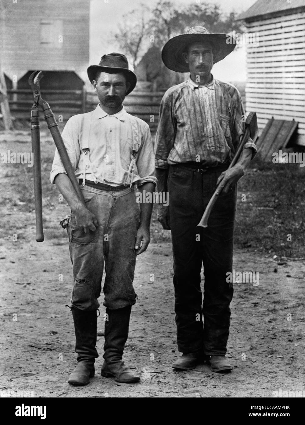 1890s 1900s 2 MEN ON FARM IN WORK CLOTHES ONE HOLDING TREE PRUNER & ONE HOLDING AX - Stock Image