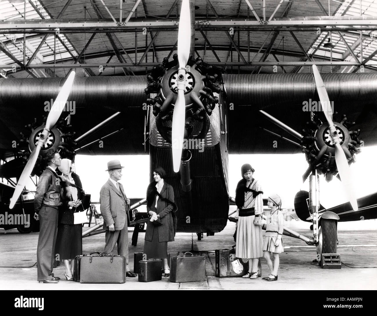 1920s 1930s GROUP OF PASSENGERS WAITING IN FRONT OF FORD TRI-MOTOR AIRPLANE Stock Photo