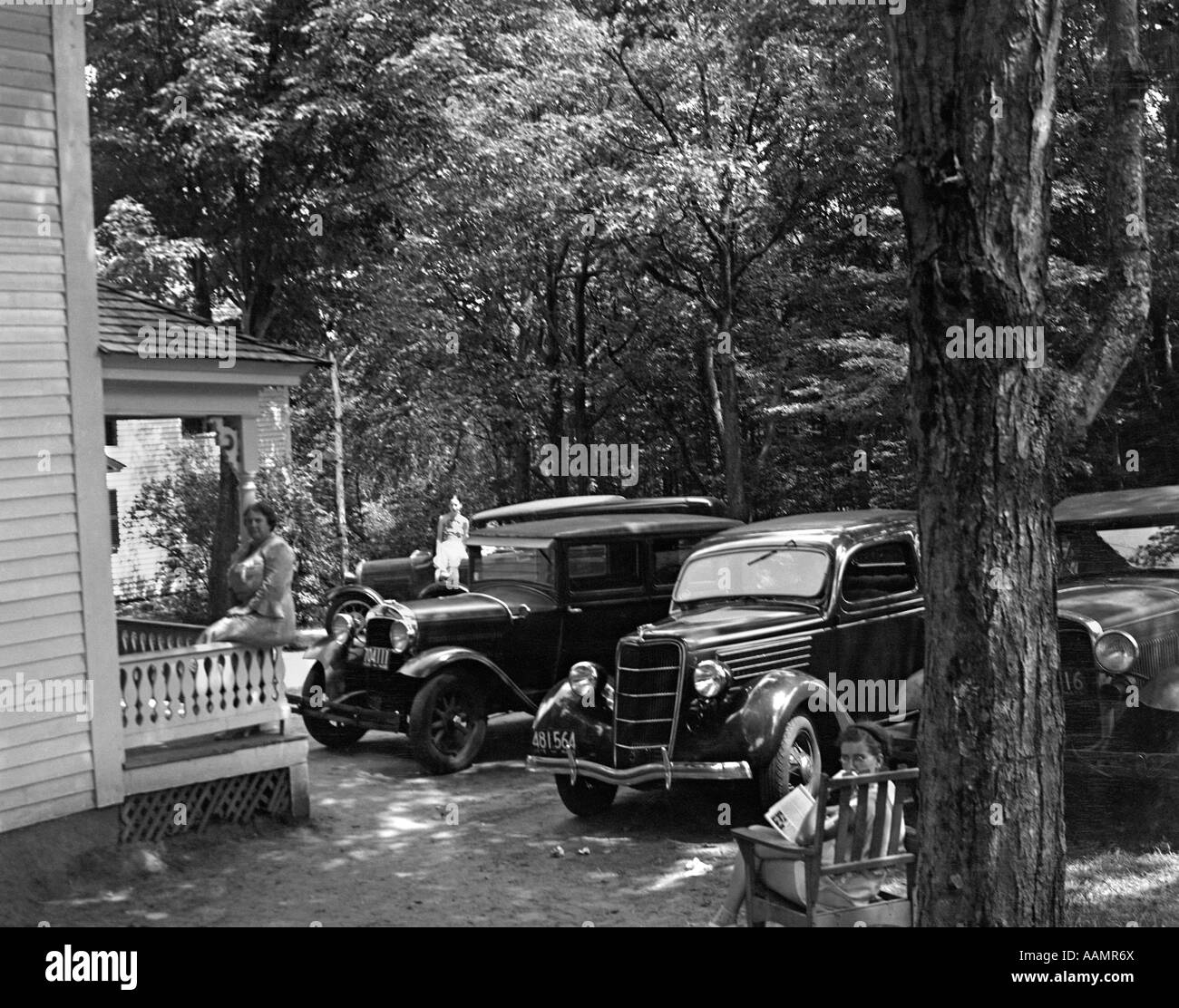 1930s CARS PARKED FRONT YARD WOMAN ON PORCH BENCH LAZY SUMMER RESORT CABIN COTTAGE NEW HAMPSHIRE USA - Stock Image
