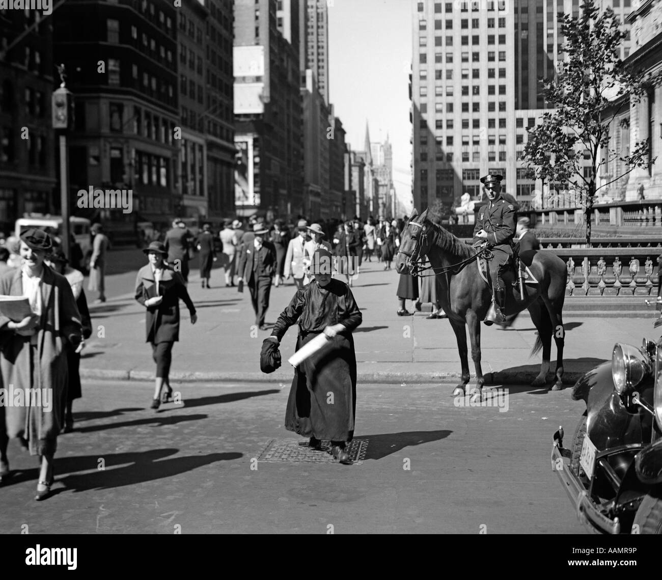 1930s MOUNTED POLICEMAN FIFTH AVENUE 40TH STREET WATCHES AS OLD WOMAN CROSSES THE STREET NEW YORK CITY USA - Stock Image