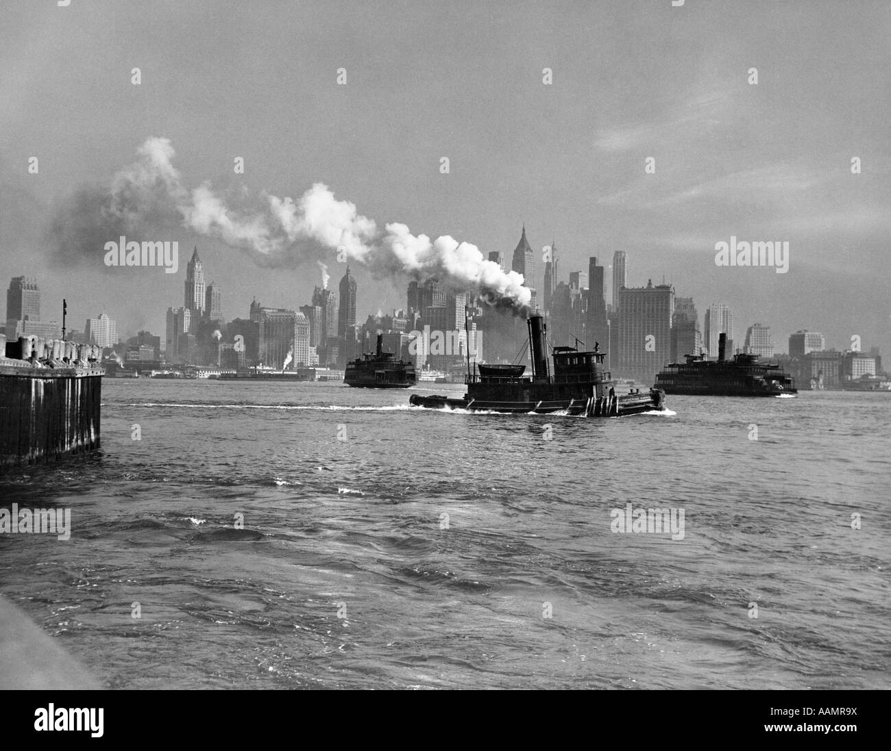 1930s 1933 STEAM ENGINE TUG BOAT AND STATEN ISLAND FERRY BOATS ON HUDSON RIVER AGAINST MANHATTAN ISLAND SKYLINE - Stock Image