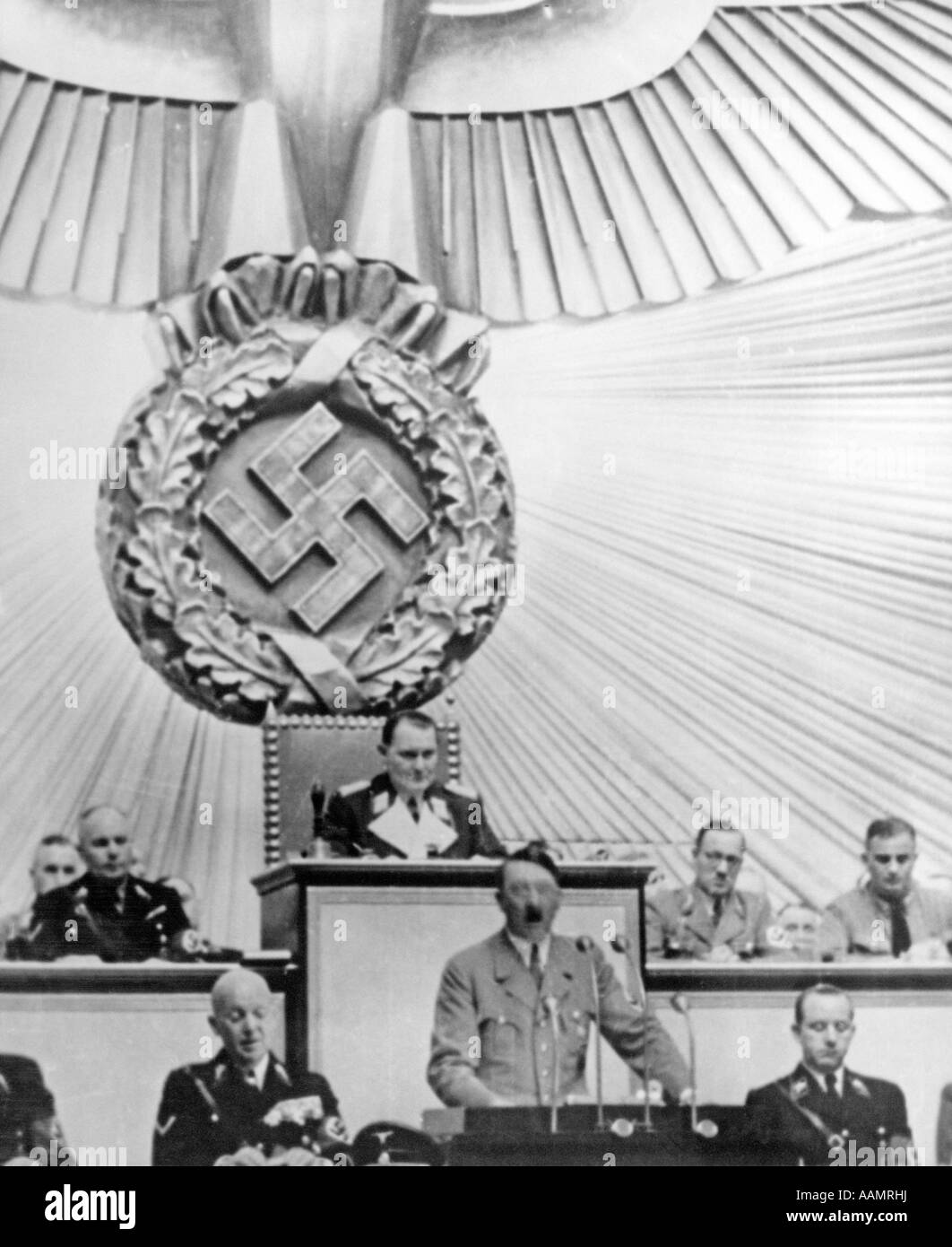 1930s ADOLPH HITLER PODIUM SPEAKING UNDERNEATH LARGE SWASTIKA AT REICHSTAG - Stock Image