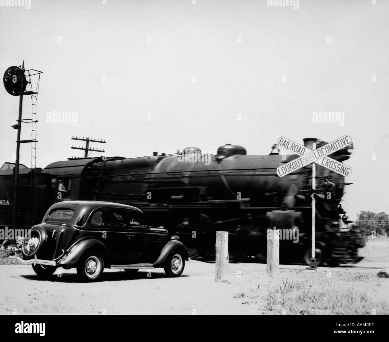 1930s CAR STOPPED AT RAILROAD CROSSING WITH FREIGHT TRAIN SPEEDING BY - Stock Image