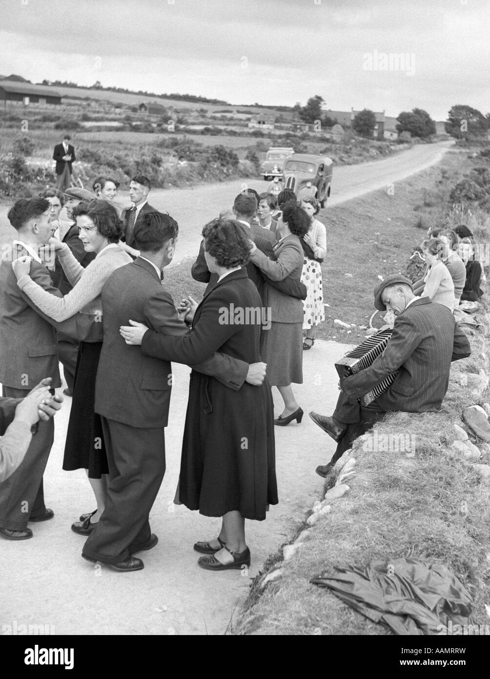 1950s GROUP OF MEN AND WOMEN DANCING IN A RURAL ROAD NEAR BANTRY IRELAND OUTDOOR - Stock Image