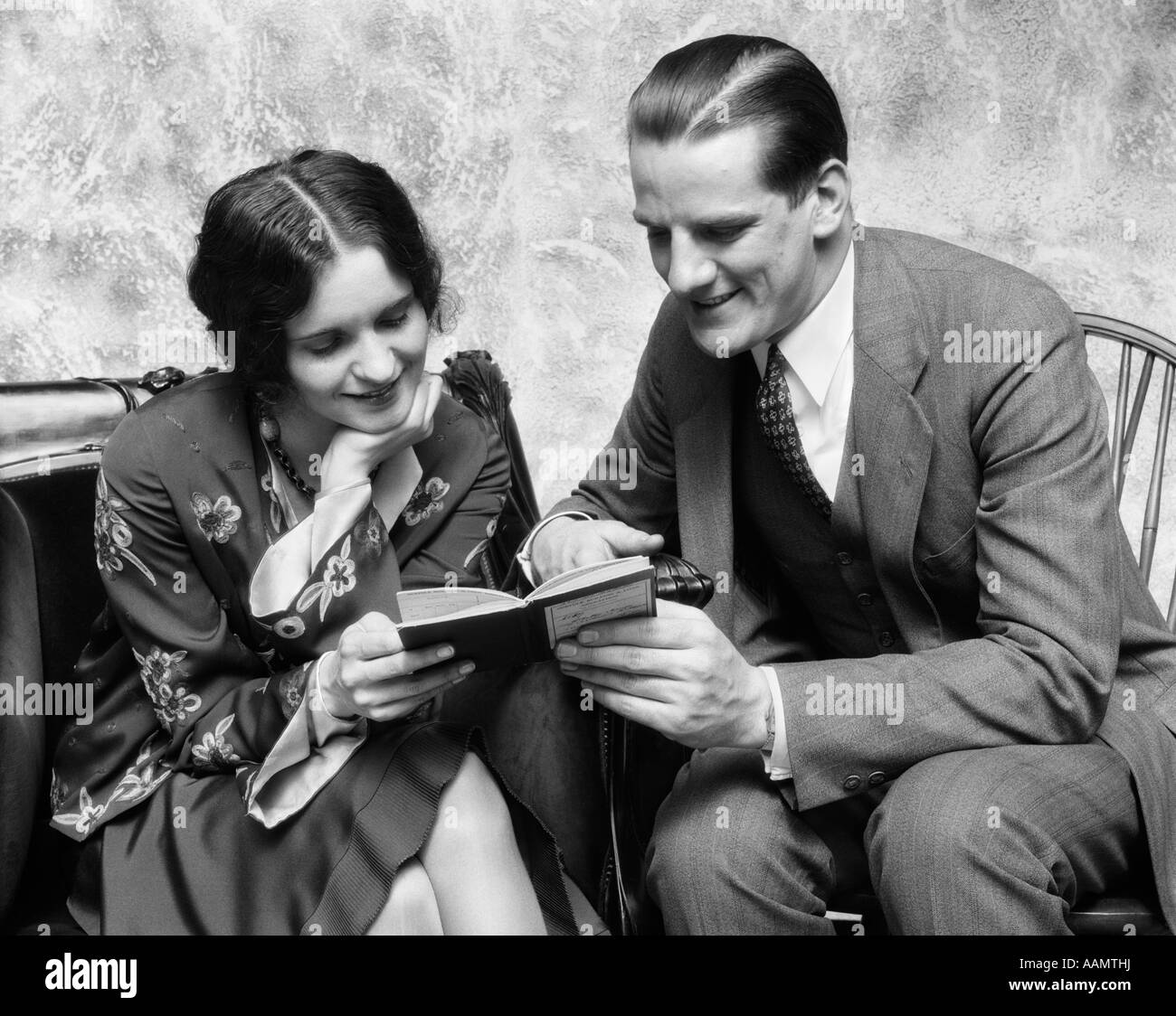 1920s 1930s COUPLE READING SHARING BOOK SMILING MAN POINTING OUT PASSAGE TO WOMAN - Stock Image