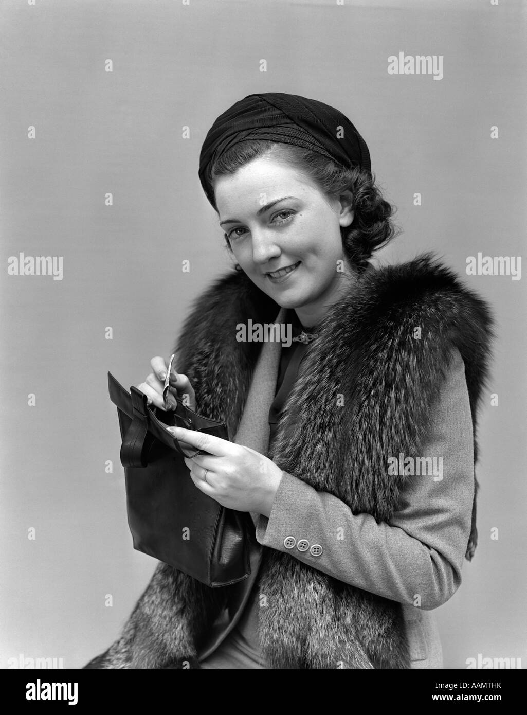 1930s 1940s WOMAN DRESSED UP WITH FUR JACKET HOLDING PURSE AND MONEY LOOKING AT CAMERA - Stock Image