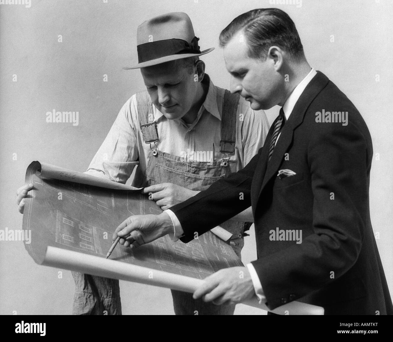 High Quality 1930s MAN ARCHITECT WEARING SUIT GOING OVER BLUE PRINTS WITH A BUILDER IN  WORK CLOTHES