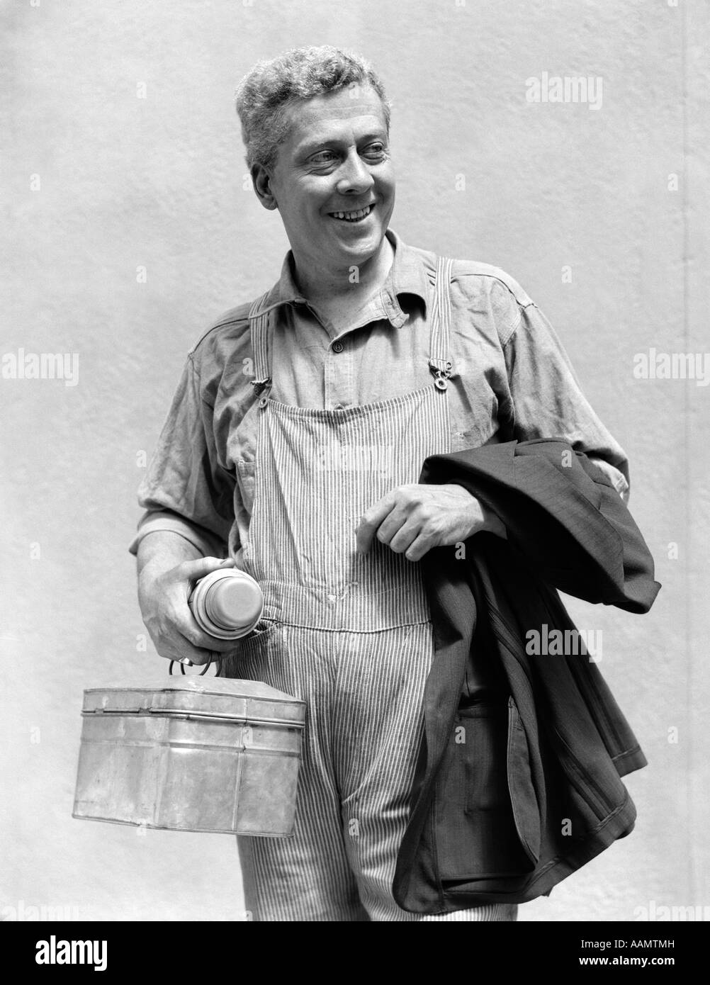 1930s MAN IN OVERALLS WORK UNIFORM HOLDING THERMOS LUNCHBOX AND JACKET - Stock Image
