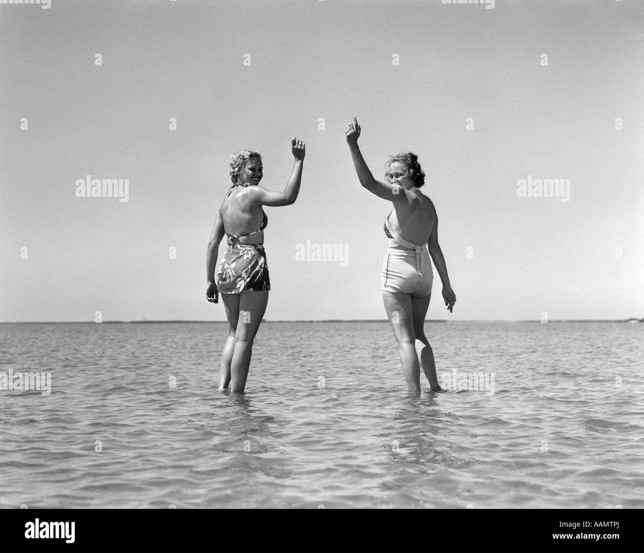 1930s TWO GIRLS STANDING IN WATER WEARING BATHING SUITS LOOKING BACK WAVING LOOKING AT CAMERA - Stock Image