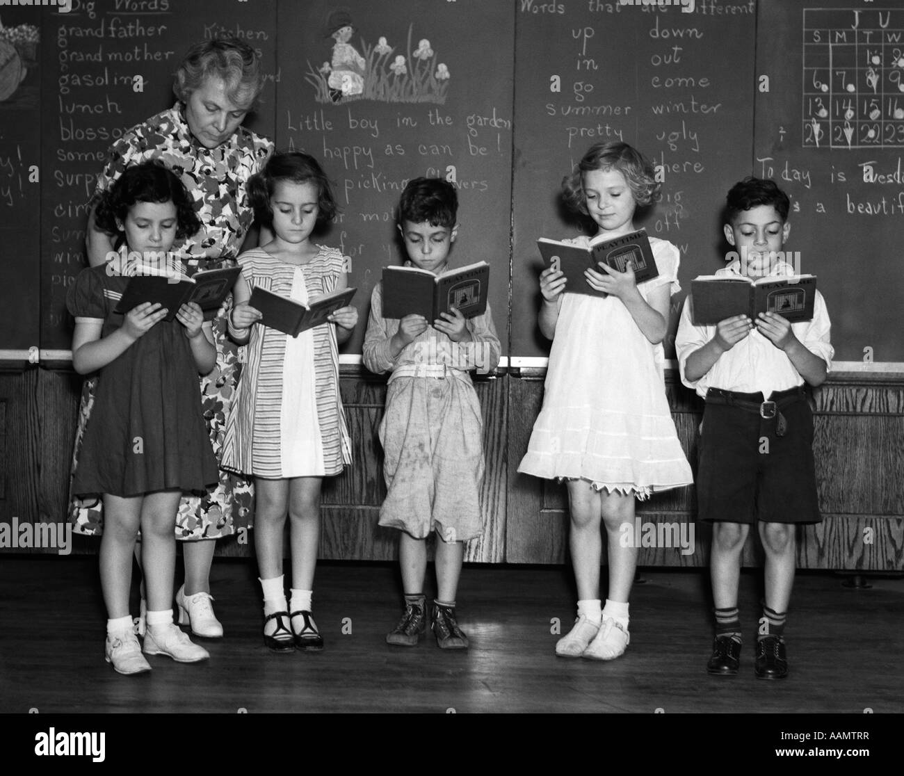 1930s LINE-UP OF 5 ELEMENTARY SCHOOL STUDENTS IN FRONT OF BLACKBOARD READING BOOKS WITH TEACHER LOOKING ON Stock Photo