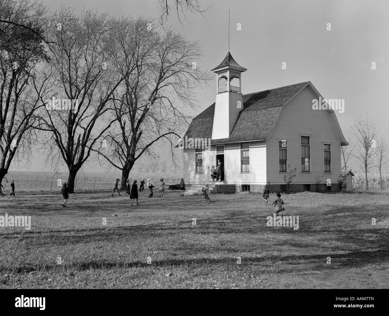 1940s RURAL ONE-ROOM SCHOOLHOUSE WITH KIDS OUTSIDE ON GROUNDS - Stock Image