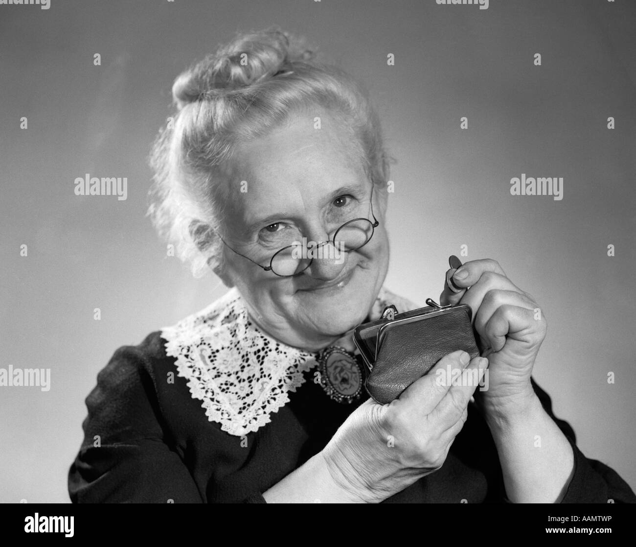 1950s PORTRAIT OF ELDERLY GRANNY PUTTING CHANGE IN PURSE - Stock Image