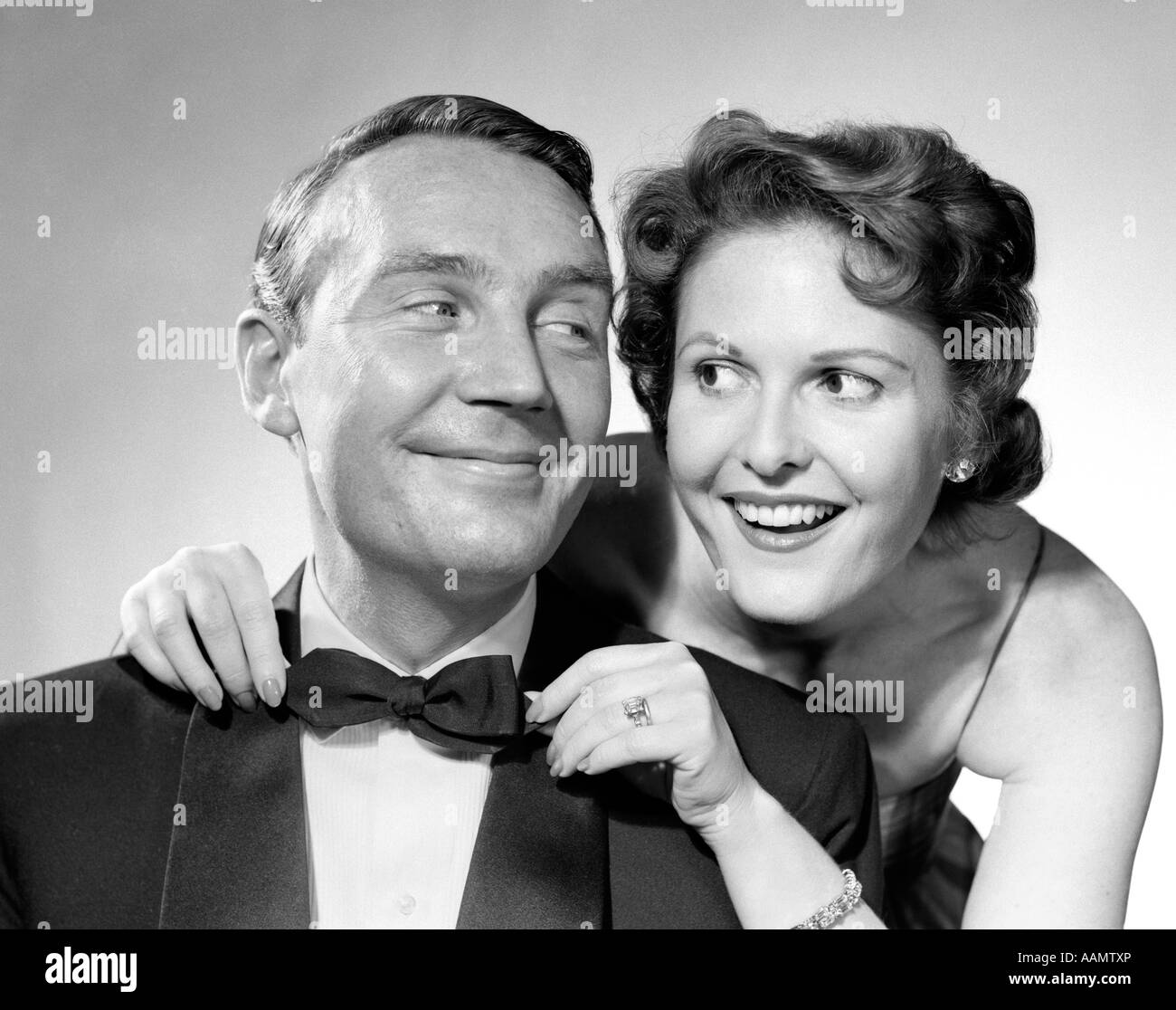 1950s 1960s SMILING COUPLE DRESSED IN FORMAL EVENING ATTIRE WOMAN PULLING ON MAN'S BOW TIE - Stock Image