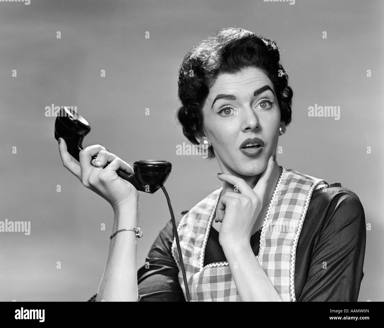 1950s WOMAN LOOKING AT CAMERA HOUSEWIFE HOLDING UP TELEPHONE RECEIVER CONFUSED FACIAL EXPRESSION - Stock Image
