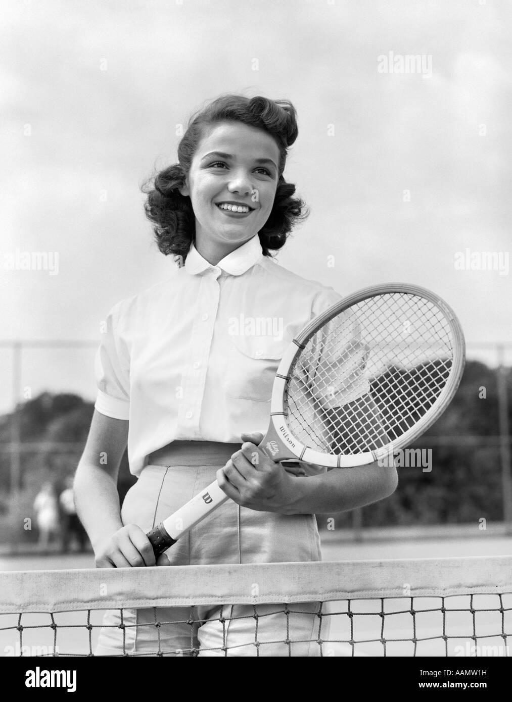 1950s 1940s WOMAN POSING WITH TENNIS RACKET ON TENNIS COURT NEAR NET - Stock Image