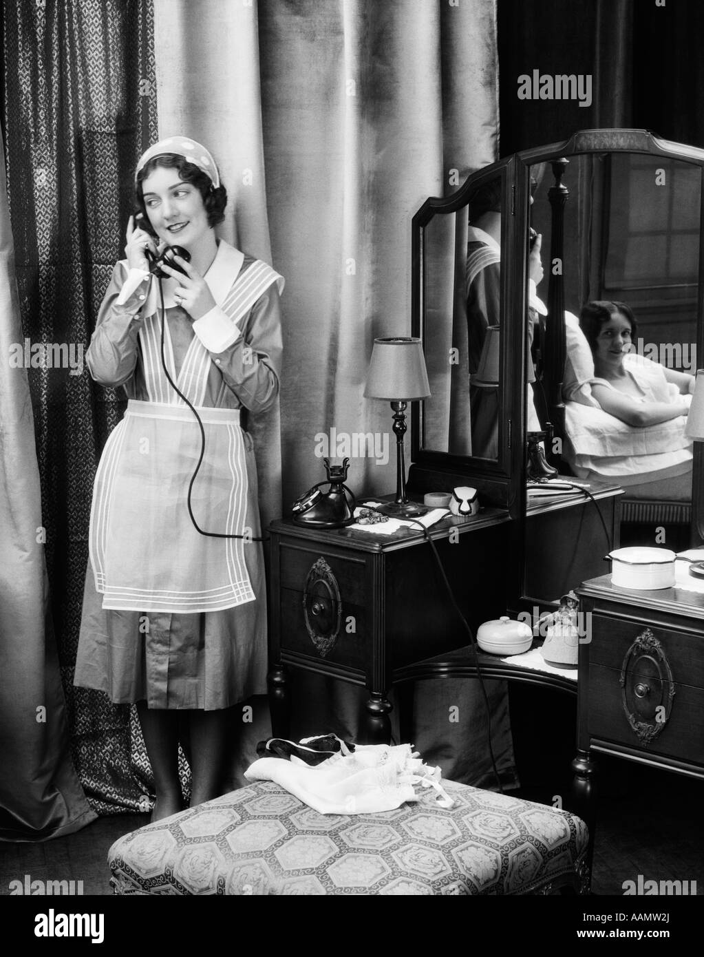 1920s 1930s MAID IN UNIFORM TALKS ON TELEPHONE IN FRONT OF VANITY DRESSING TABLE OTHER WOMAN IS SEEN AS REFLECTION - Stock Image