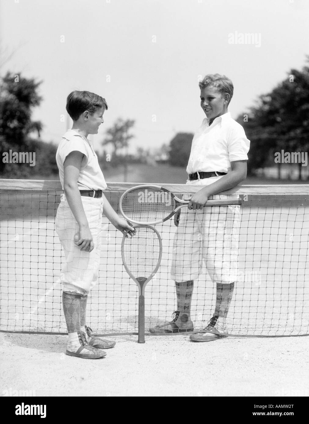 1920s 1930s TWO BOYS TENNIS MATCH HOLDING RACKETS MEASURING NET HEIGHT - Stock Image
