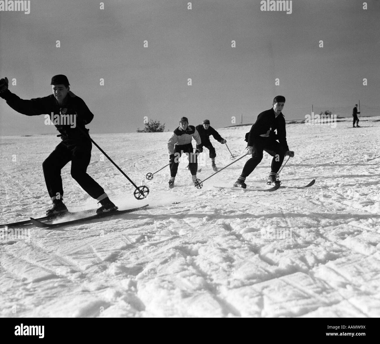 1930s GROUP OF YOUNG MEN SKIING DOWNHILL Stock Photo