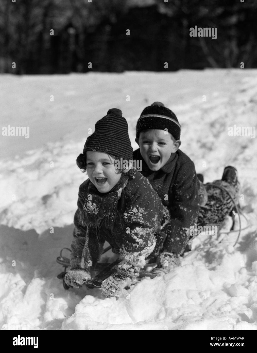 1930s BOY AND GIRL LAUGHING SLEDDING IN SNOW - Stock Image