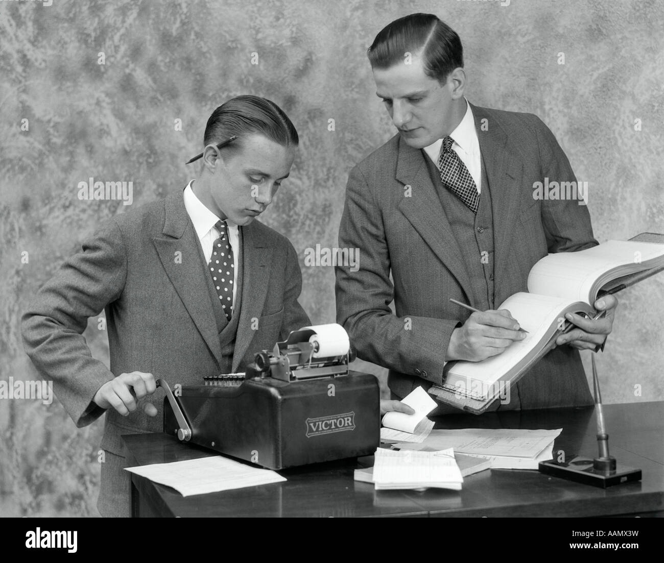 1930s Clerk And Young Assistant In Office Using Ledger