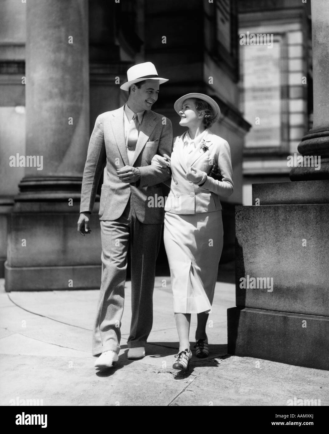 1930s COUPLE IN SUITS AND HATS WALKING ARM IN ARM - Stock Image