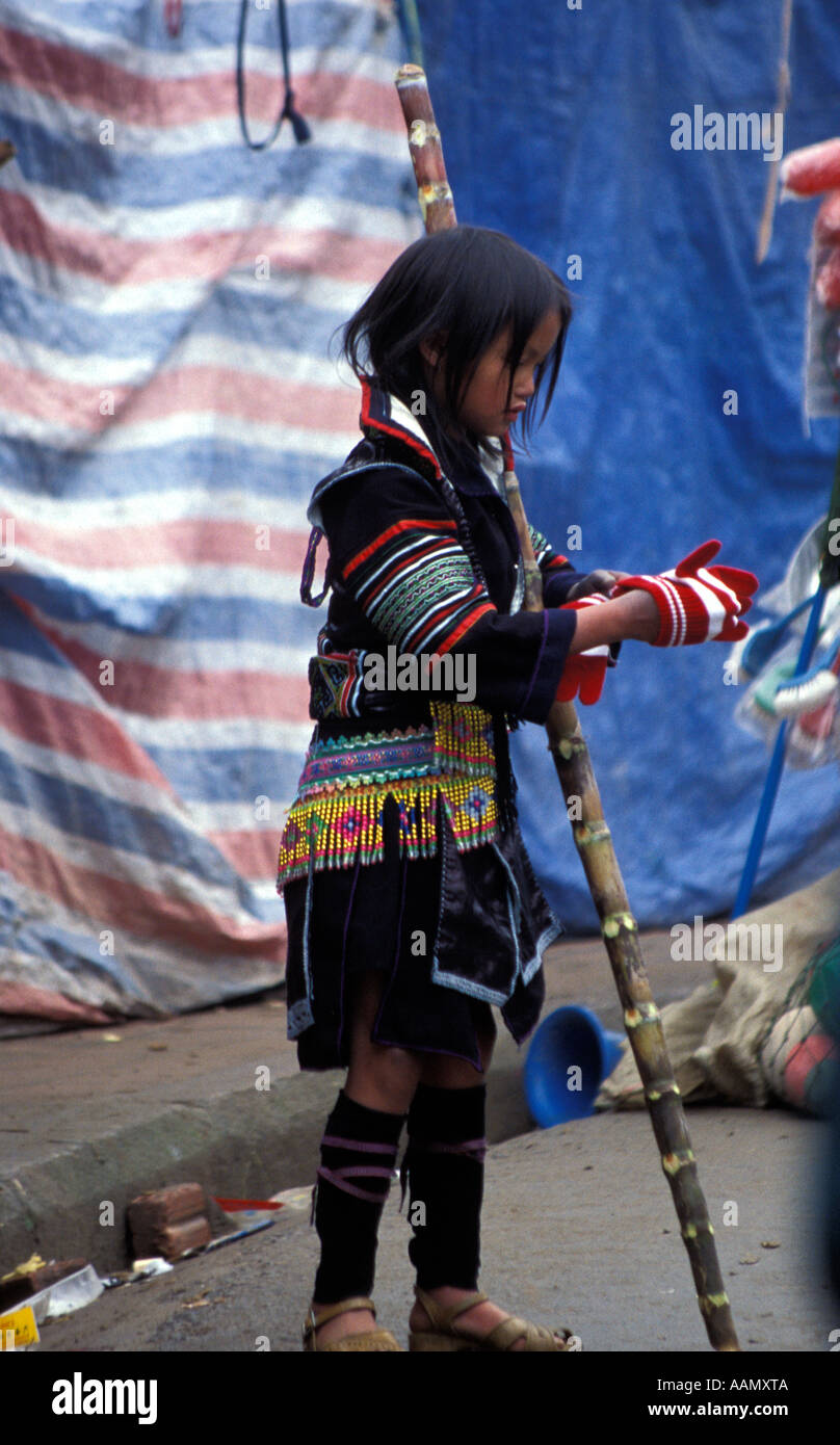Young Black Hmong ethnic minority girl trying on new gloves, Sapa, Tonkinese Alps, North Vietnam Stock Photo