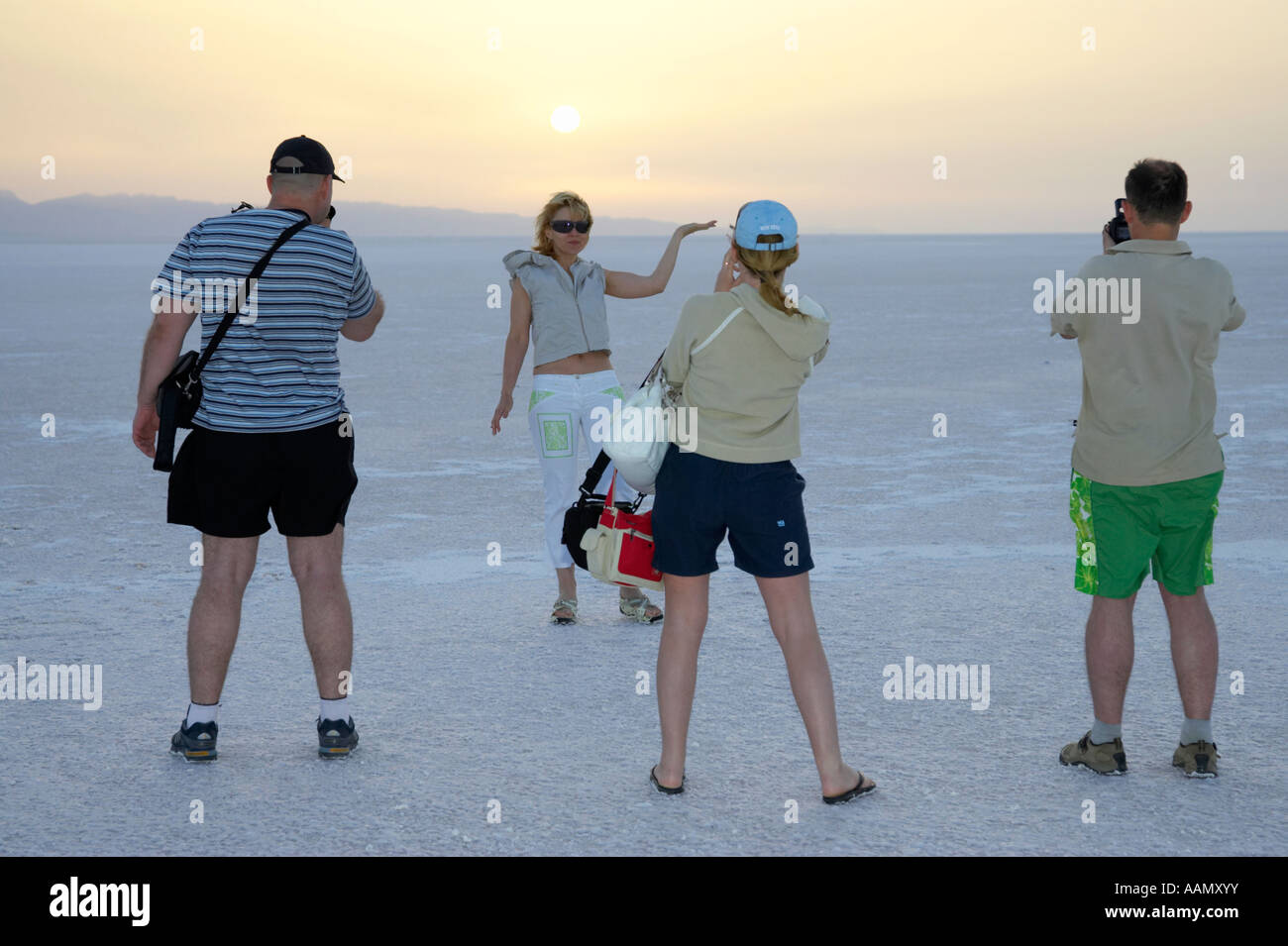 group of tourists take photos of the sun rising over chott el djerid tunisia - Stock Image