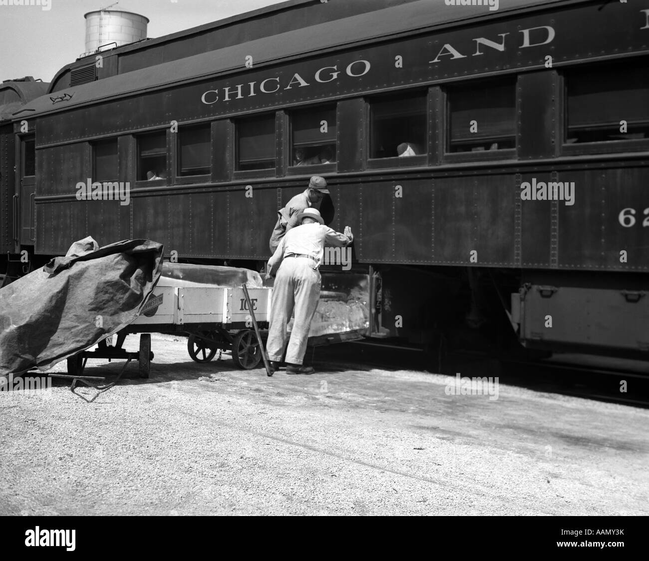 1930s 1940s TWO RAILROAD WORKERS PUTTING CAKES OF ICE INTO CLIMATE CONTROL AIR CONDITIONING COMPARTMENTS OF PASSENGER - Stock Image