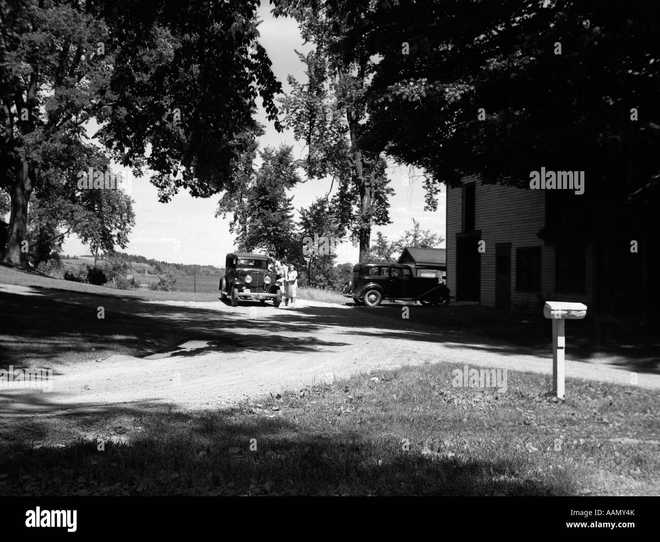 1930s TWO CARS PARKED COUNTRY HOUSE RURAL MAIL BOX RIGHT QUIET TOWN OF VEAZIE NEAR BANGOR MAINE - Stock Image