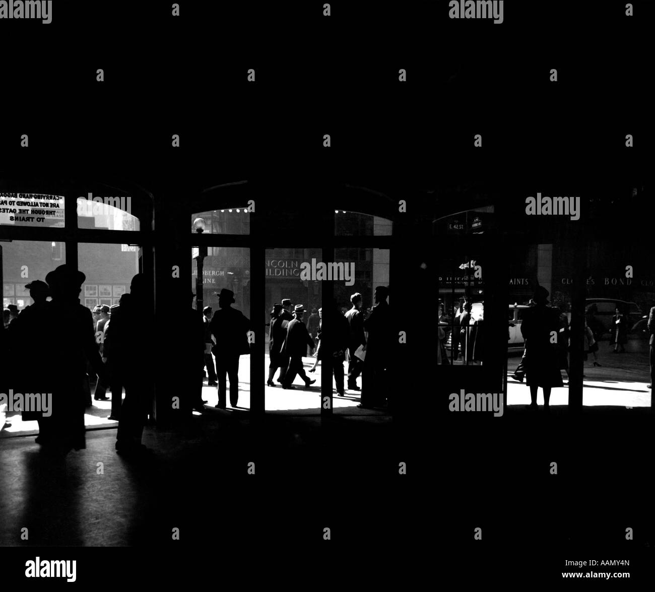 1930s SILHOUETTED PEDESTRIANS & TRAFFIC OUTSIDE THE DOORS OF GRAND CENTRAL STATION MANHATTAN NEW YORK - Stock Image