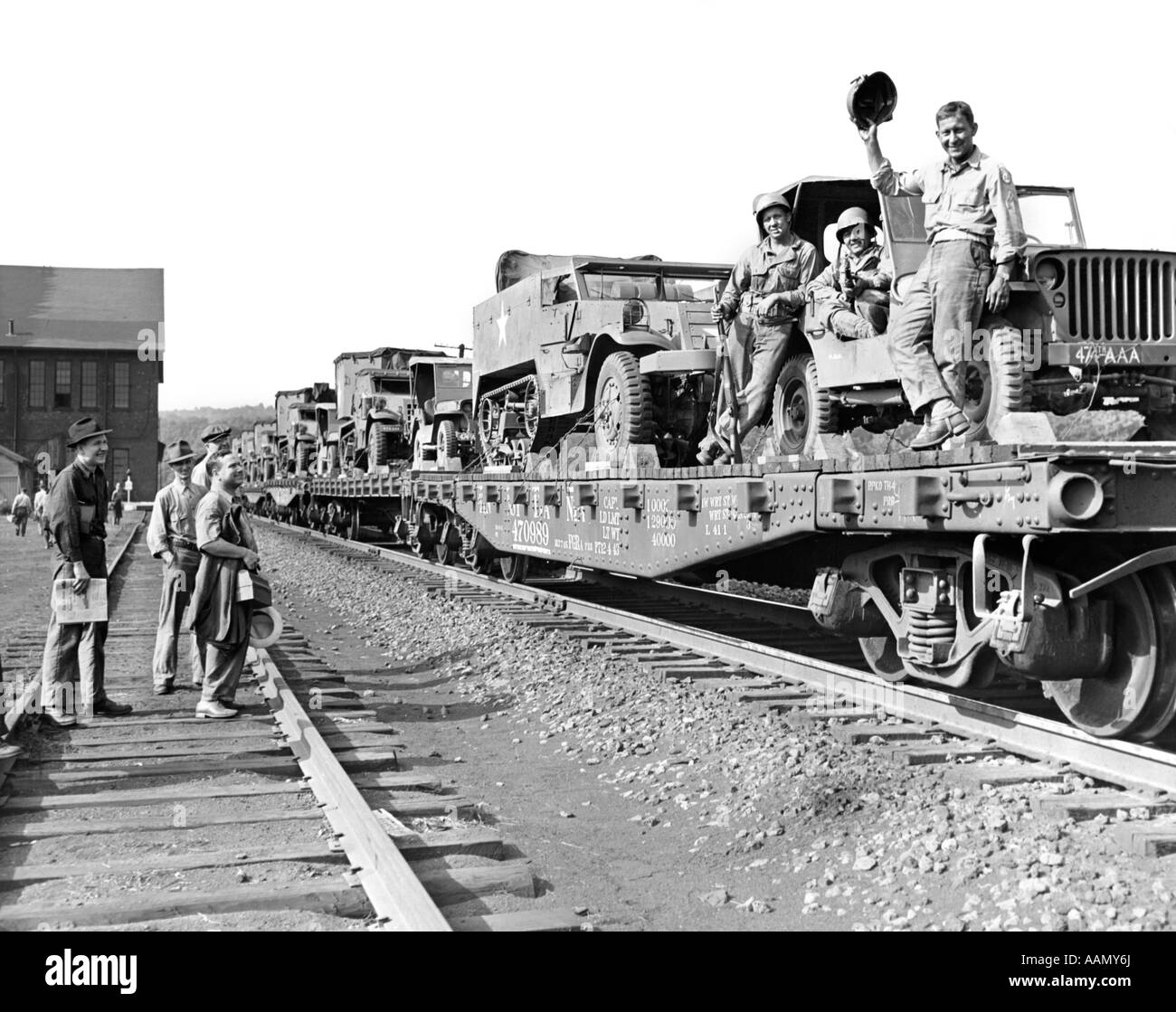 1940s WORLD WAR II FREIGHT TRAIN OF JEEPS AND HALF TRACKS ON WAY TO THE FRONT FACTORY WORKERS BID FAREWELL TO SOLDIERS - Stock Image