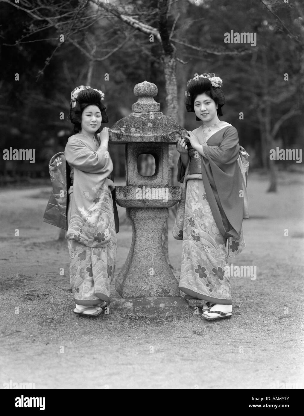 1930s TWO JAPANESE GEISHA GIRLS IN NATIVE COSTUME KIMONO STANDING BY STONE LANTERN KOBE JAPAN - Stock Image
