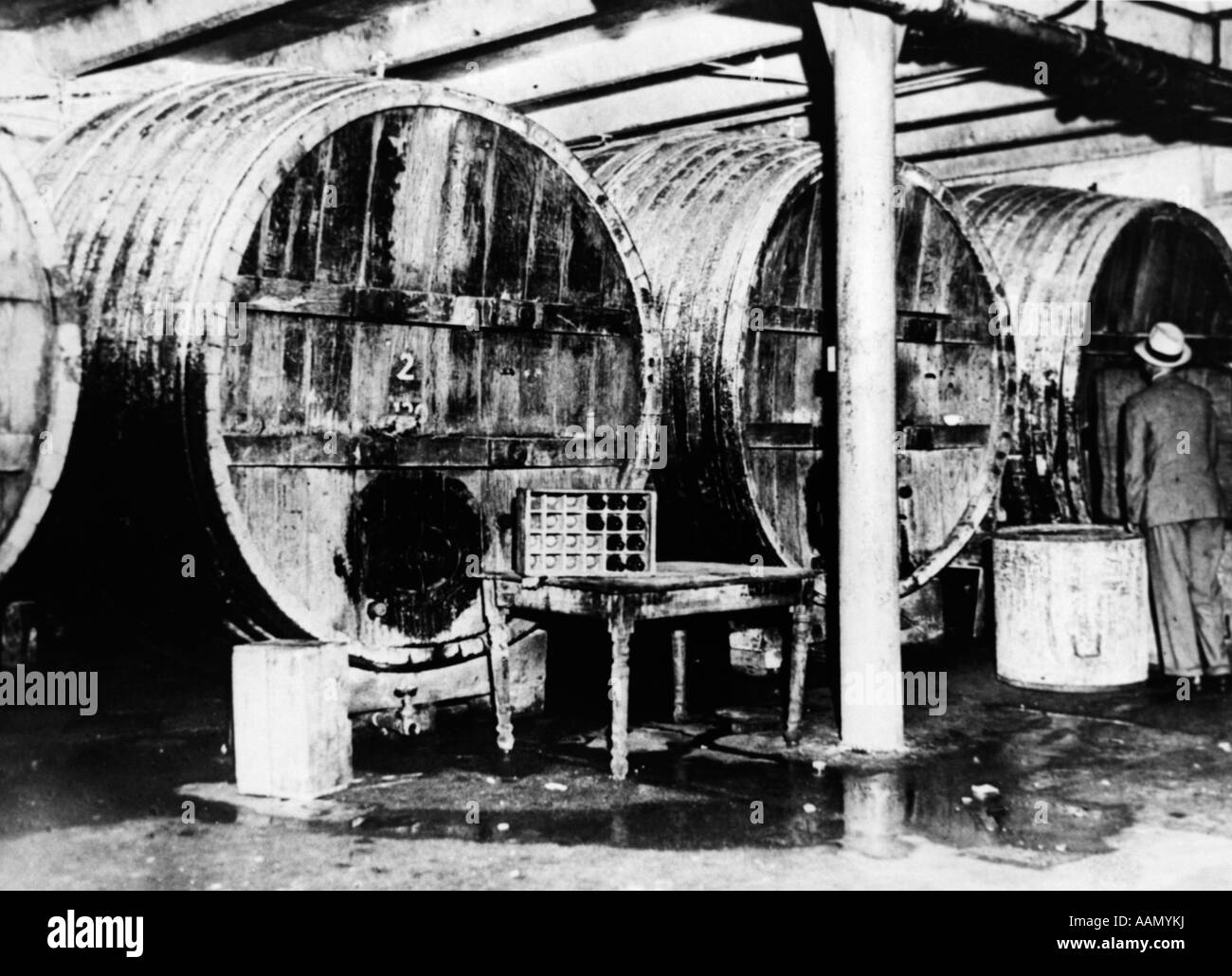 1920s 1930s PROHIBITION FEDERAL AGENT STANDS BESIDE BEER BATS AT ILLEGAL DISTILLERY IN ONE OF LARGEST RAIDS JULY - Stock Image